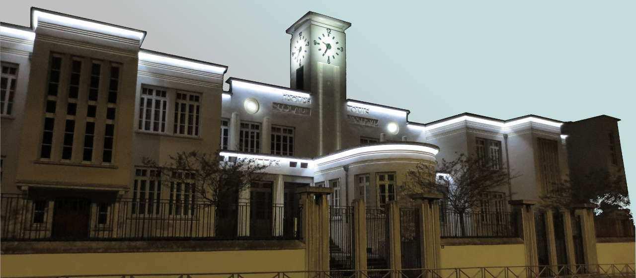 Photo de l'école Pasteur de Vénissieux de nuit, mise en valeur par son éclairage